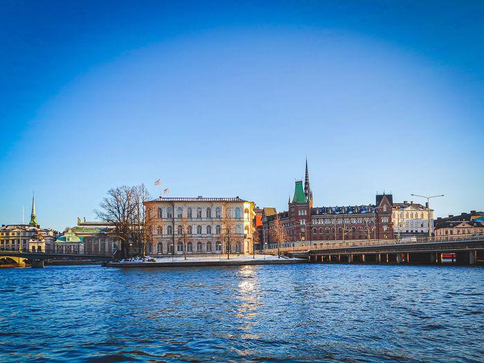 River by buildings against blue sky