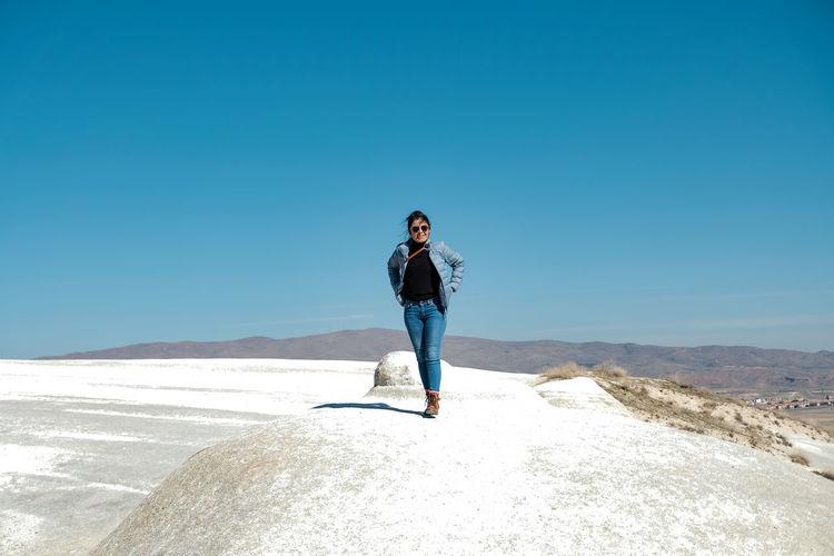 Full length of woman against blue sky on sunny day