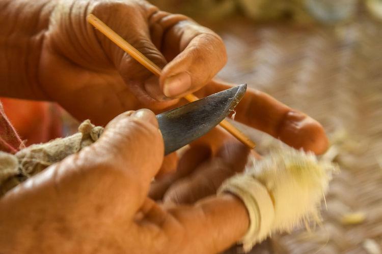 Cropped Hands Of Craftsperson Holding Knife At Workshop