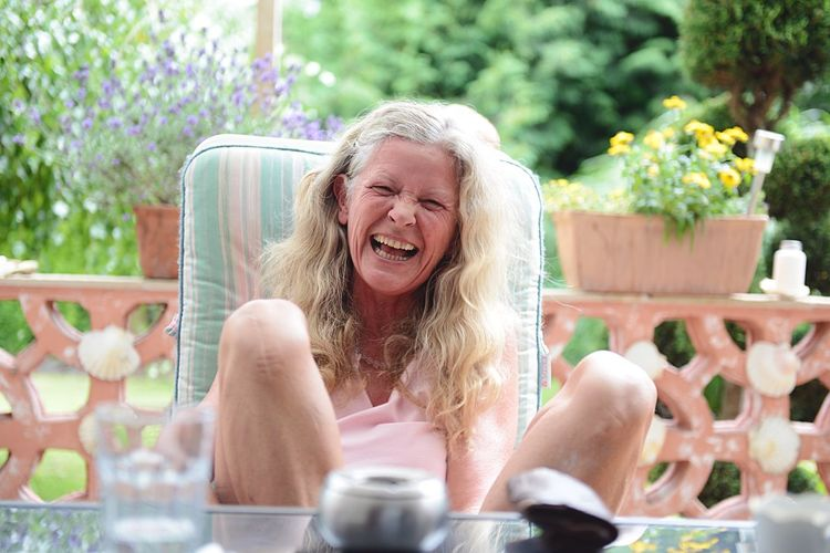 Cheerful Mature Woman Sitting On Porch