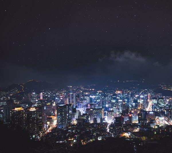 Illuminated cityscape against star field sky at night