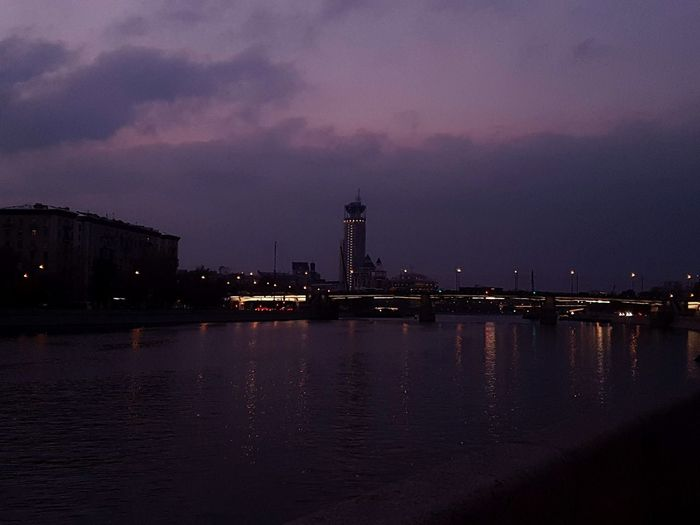 Illuminated buildings by river against sky at sunset