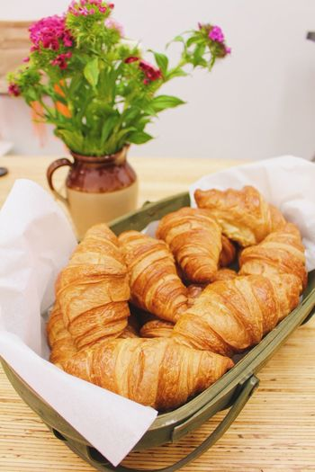 Close-up of fresh croissants in tray by vase on table