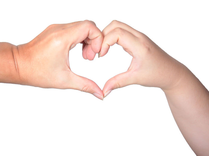 Couple hands do a heart shape against white background Human Hand White Background Studio Shot Human Finger Close-up Symbol Gesturing Isolated White Background Sign Concept Communication Heart Shape Love Positive Emotion Women Hole Like Letter Give Flirting Happy Couple Relationship