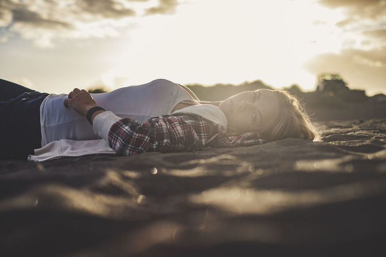 Surface Level View Of Young Woman Lying At Beach During Sunset