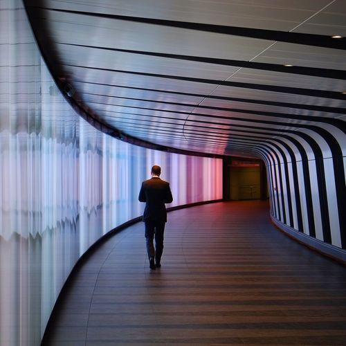 Rear view full length of businessman walking in modern building corridor