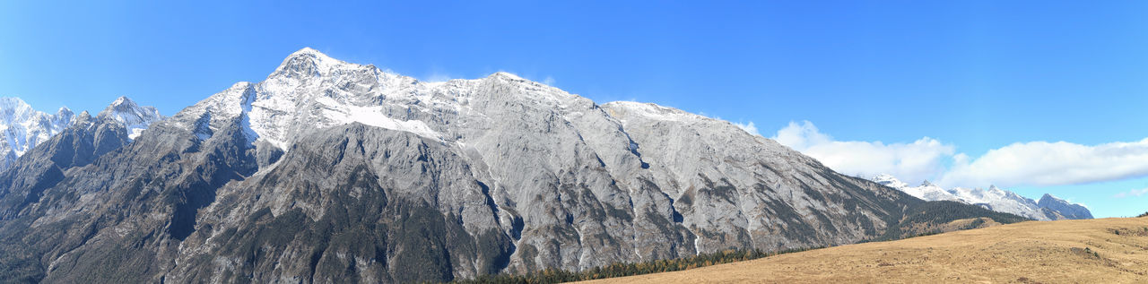 Low Angle View Of Snow Covered Mountain Against Blue Sky