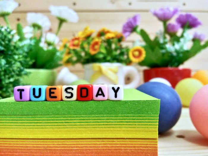Close-up of colorful blocks with tuesday text on stacked papers over table