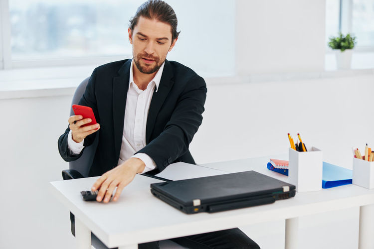 Young man using mobile phone while sitting on table