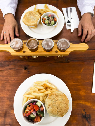 Cropped Image Of Person Having Beer With Burger And French Fries On Table