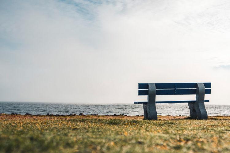 Bench on beach by sea against sky