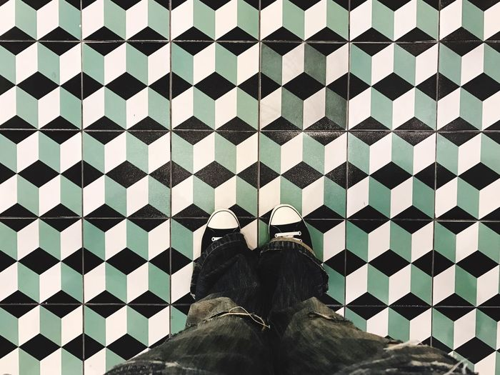 Low section of man standing on patterned tiled floor