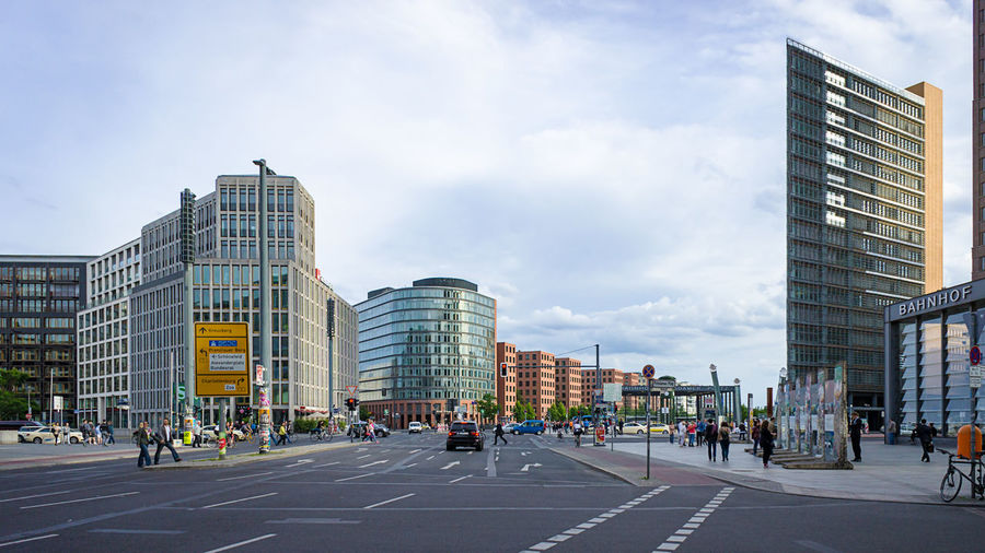 Road amidst modern buildings at potsdamer platz against sky