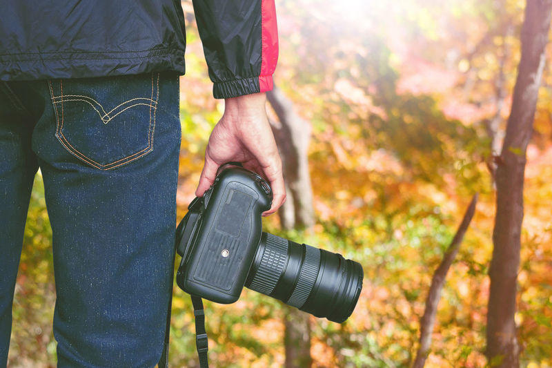 Midsection of man holding camera while standing in forest