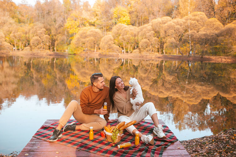 Young couple sitting on lake during autumn