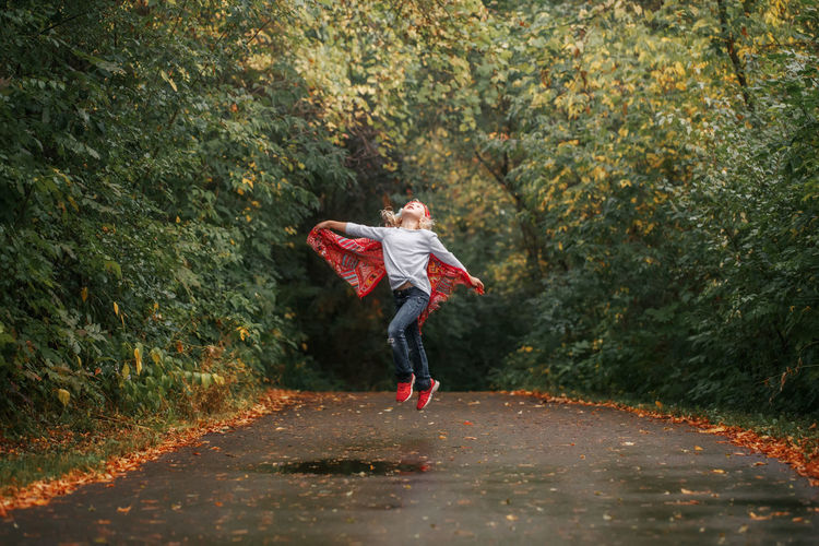 Girl jumping on road against trees in forest