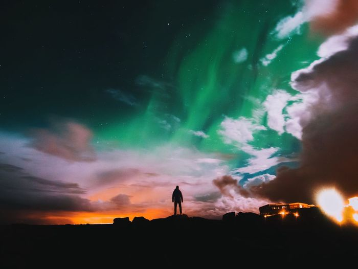Silhouette Man Standing On Rock By Aurora Borealis Against Cloudy Sky At Night