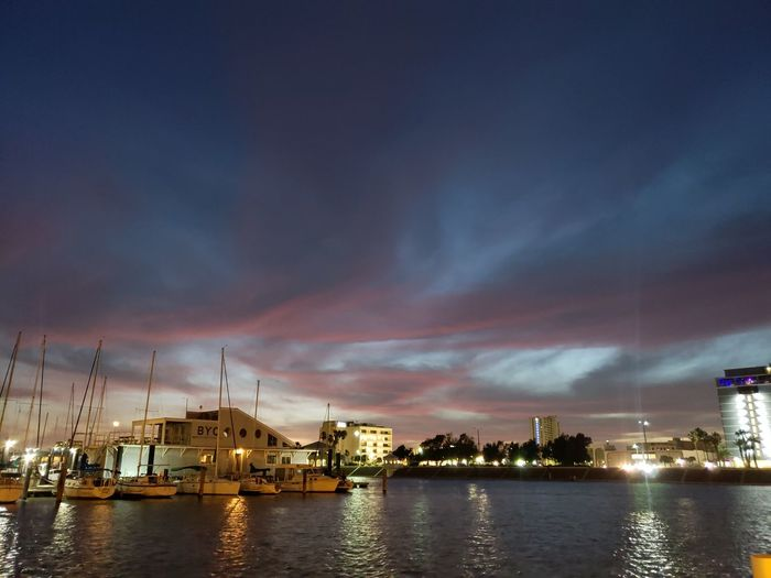 Illuminated buildings by sea against sky at sunset