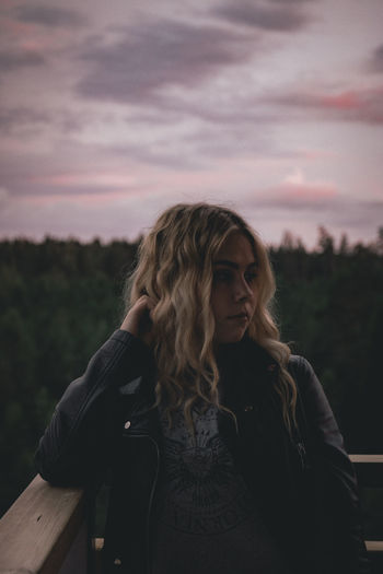 Thoughtful young woman standing against sky