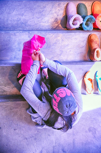 High angle view of girl sitting on pink floor