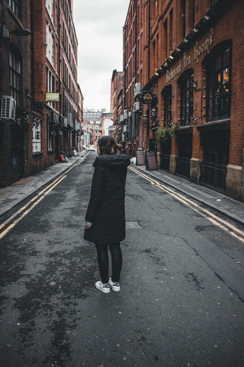Rear view of woman walking on road amidst buildings in city
