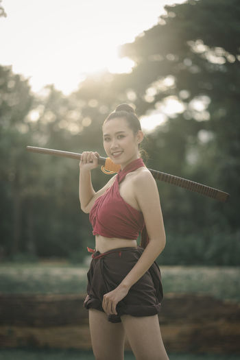 Portrait of young woman holding wooden sword while standing against trees