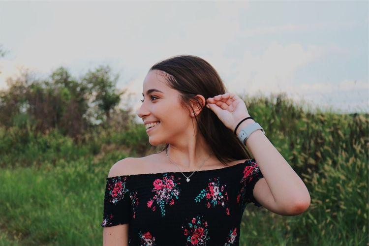 Smiling Teenage Girl Standing On Field