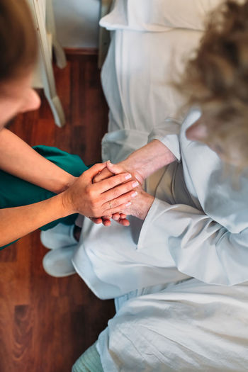 Female doctor giving encouragement to elderly patient by holding her hands Bed Care Doctor  Holding Hands Hospital Loving Nursing Woman Aged Clinic Elderly Encouragement Examining Health Care Healthcare And Medicine Home Assistance Home Assistant Illness Medical Nursing Home Patient Senior Treatment Two People Vertical