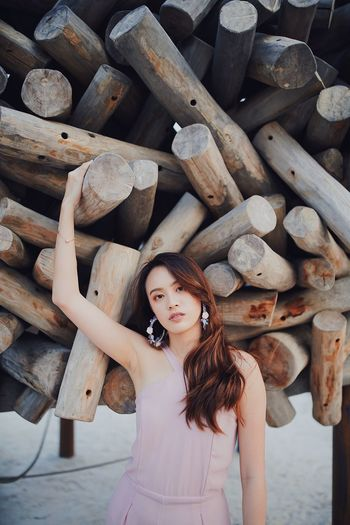 Portrait of young woman standing on wooden logs