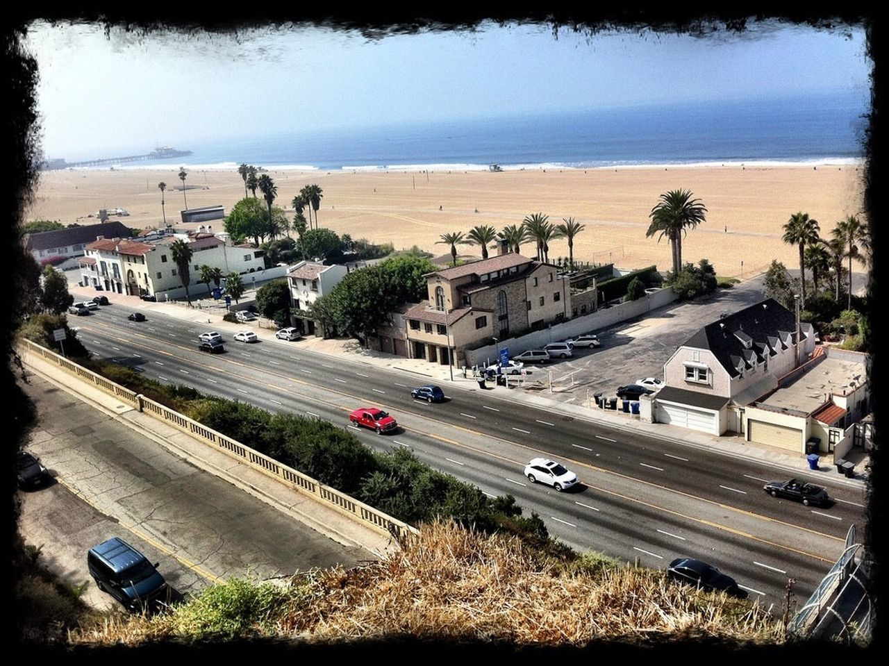 High angle view of cars on street by beach against blue sky