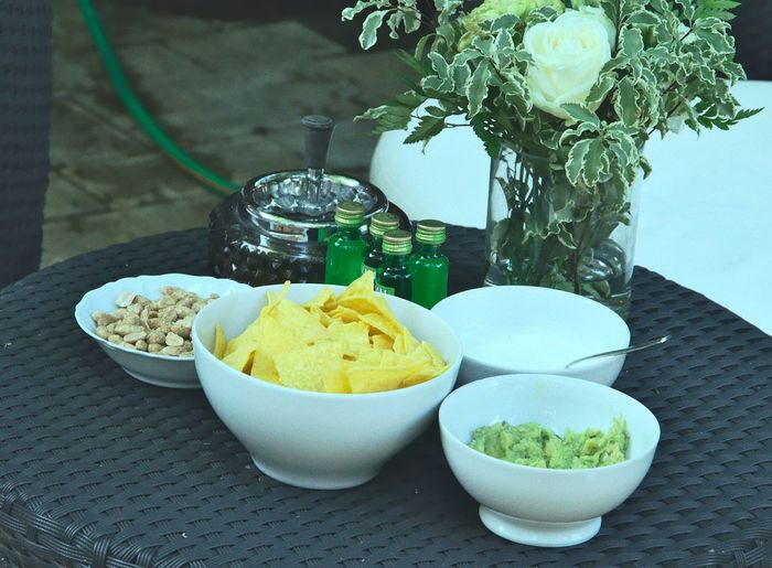 High Angle View Of Guacamole Served With Tortilla Chips And Peanuts In Bowl On Table