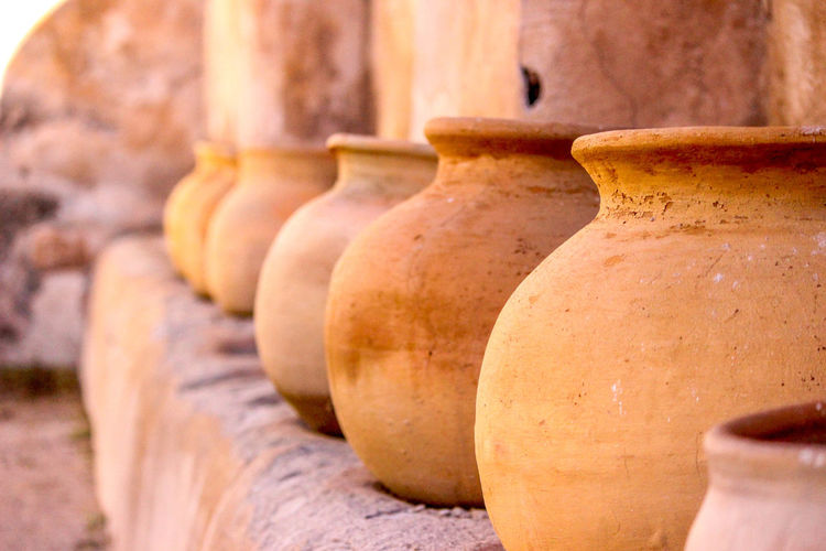Clay Pots In Row By Wall For Sale At Market