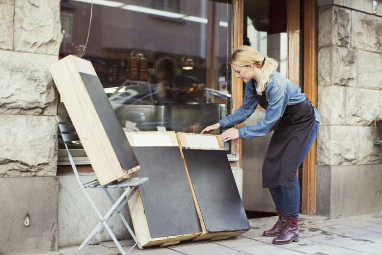Side view of woman working at store