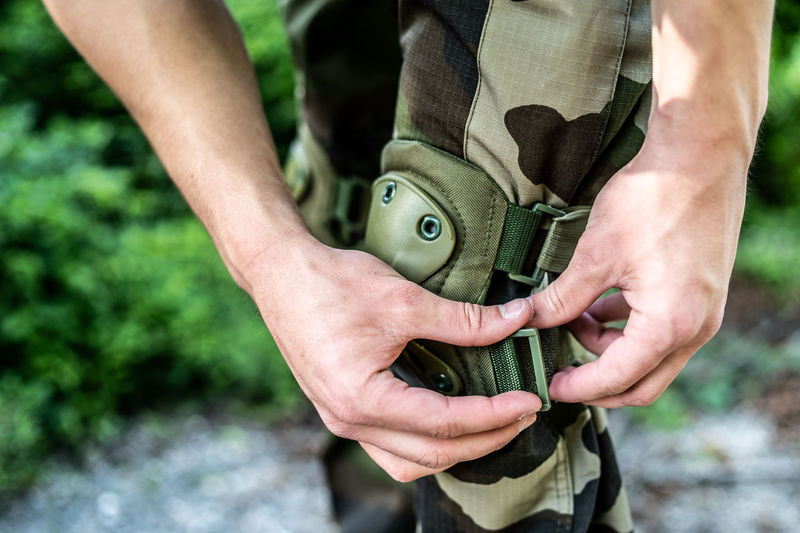 Midsection of army soldier wearing knee protector