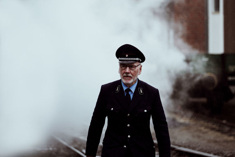 MASTER OF CEREMONY Smoke Uniform Adult Business Clothing Communication Conductor Day Fog Front View Glasses Government Looking At Camera Males  Men One Person Portrait Security Senior Adult Senior Men Smoke - Physical Structure Standing Train Waist Up Well-dressed The Street Photographer - 2018 EyeEm Awards