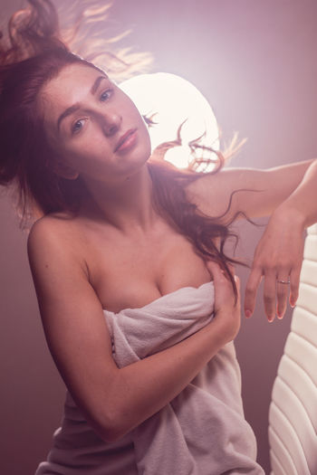 Portrait Of Sensuous Woman Wrapped In Towel Against Window