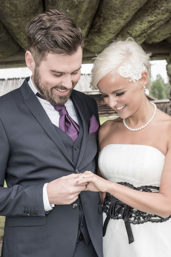 Smiling Bride And Groom Looking At Wedding Ring
