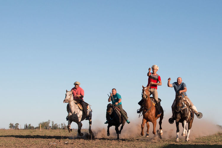Group of people riding on field against clear sky
