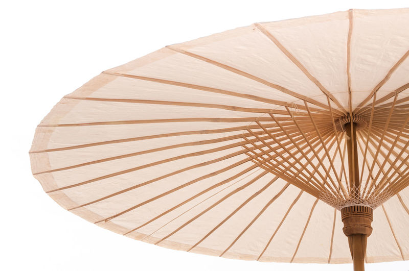 Traditional Asian paper and bamboo umbrella with a rounded handle on white background Bamboo - Material Bamboo - Plant Beach Umbrella Ceiling Clear Sky Close-up Day Indoors  Low Angle View Paper Parasol Pattern Protection Safety Security Shade Shelter Single Object Studio Shot Sunshade Traditional Umbrella Umbrellas Umbrella☂☂ White Background