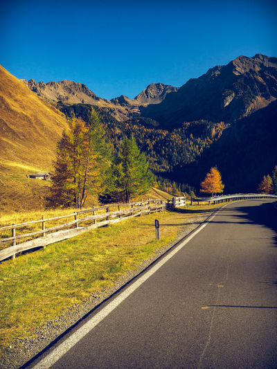 Mountain road up to Penser pass accompanied with larch trees. Penser Joch Passo Pennes Mountain Landscape Nature Sky Scenics - Nature Environment Plant Beauty In Nature No People Mountain Range Tranquil Scene Tranquility Outdoors Larch Road Transportation Autumn Direction Tree The Way Forward Symbol Land Change Dividing Line