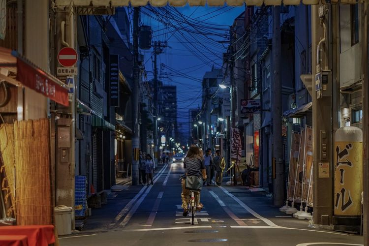 Cyclist Japan Architecture Bicycle Building Building Exterior Built Structure Cables City Illuminated Kyoto Kyoto,japan Lifestyles Men Motion One Person Real People Rear View Road Street Streetphotography The Way Forward Transportation Urbanphotography Walking