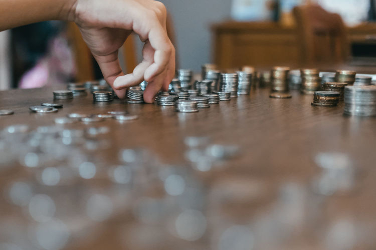 Cropped hand of person stacking coins on table