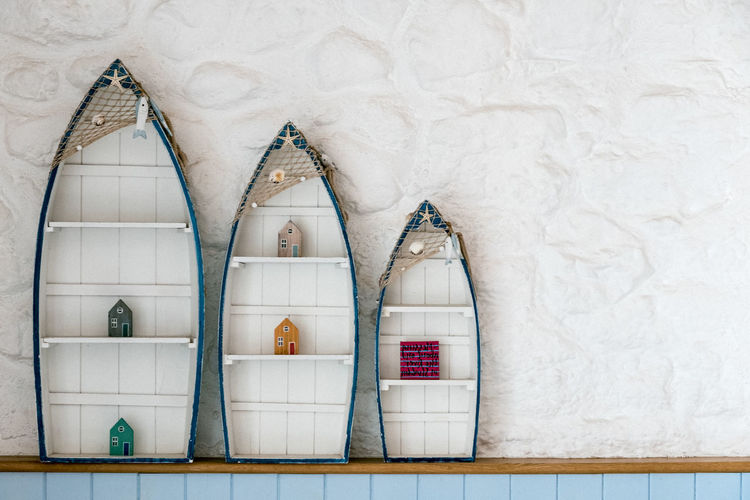 Three different sized ornamental fishing boats on a shelf. Bookshelf Fishing Boats Ornamental Boats Cabinet Decrative Fishing Fishing Nets Indoors  Nautical Theme Nautical Vessel Nautical Vessels No People Seaside Shelf Three Whitewashed