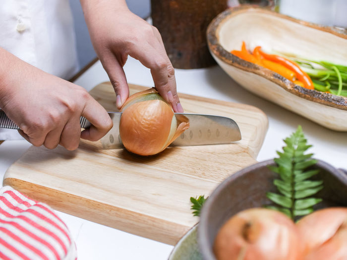 Midsection of woman preparing food on cutting board