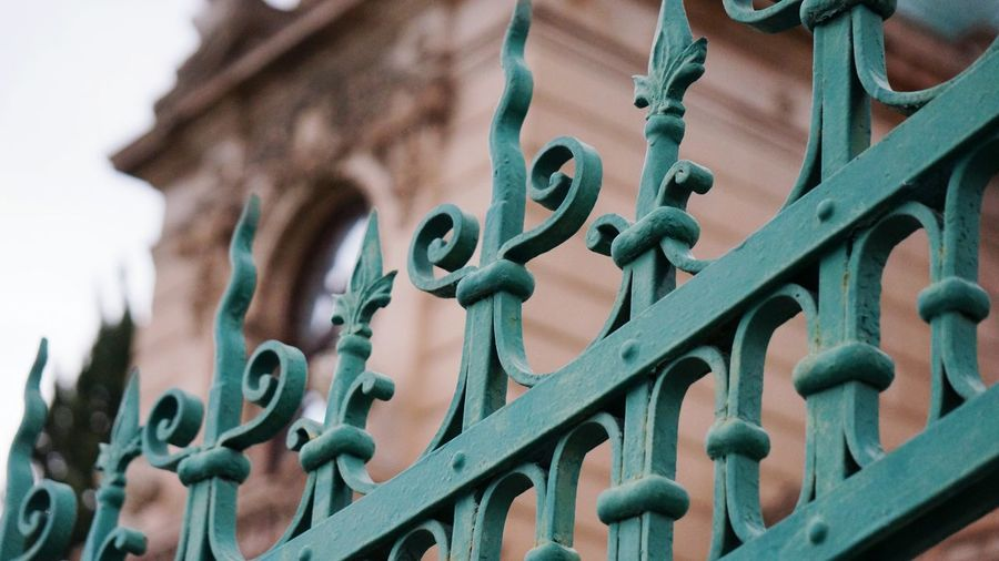 Close-up of metallic fence against historic building