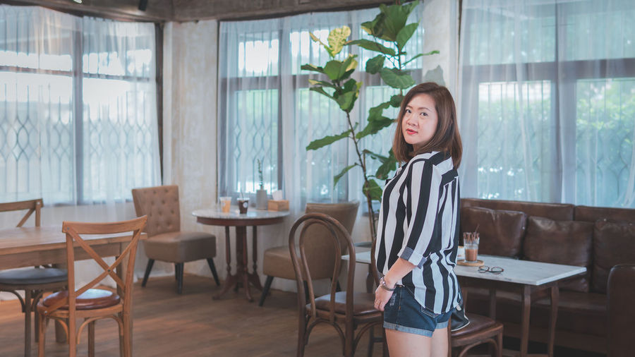 Smiling Woman Standing On Chair In Restaurant