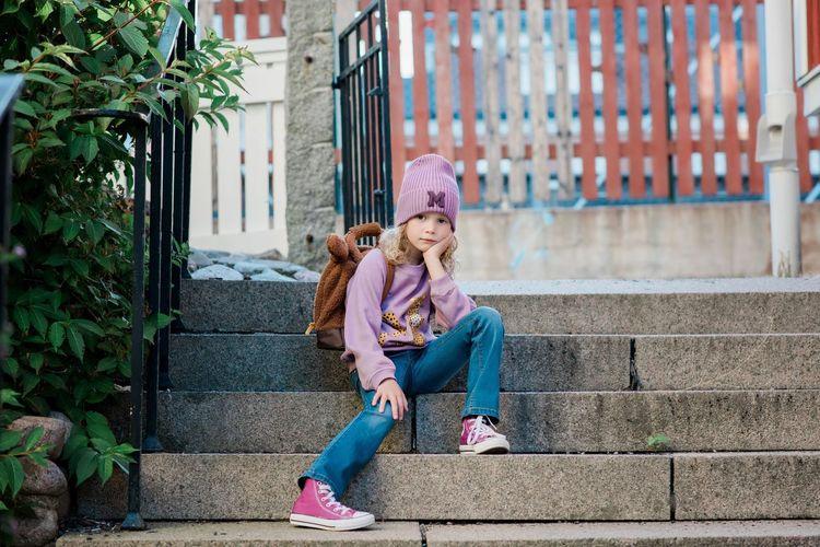 Full length of girl sitting on staircase