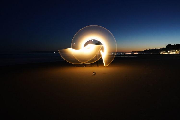Man standing by illuminated lighting equipment at beach against sky at night