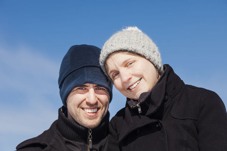 Portrait of smiling couple standing against blue sky during winter