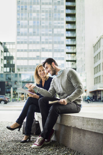 Young couple sitting on wall in city